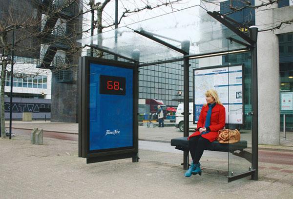 Publicidade em abrigo de ônibus que mostra o peso das pessoas que sentam nos bancos